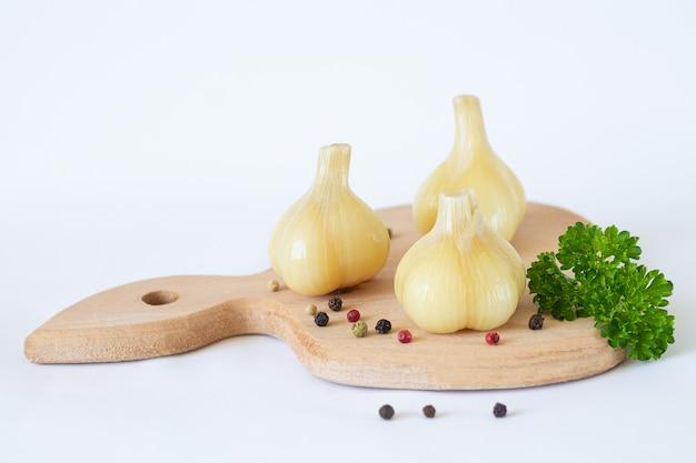 ハーブとスパイスを白で隔離される木の板にマリネまたは発酵したgarlik