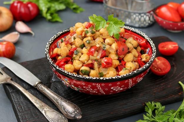 ひよこ豆にコショウとトマトを飾る、たんぱく質が豊富なベジタリアン料理を皿に盛り付けます