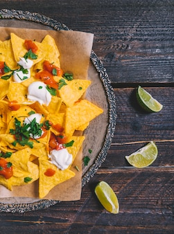 Garnished tasty mexican nachos in plate with lemon slices on wooden table