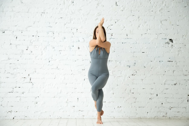 Garudasana pose、白いスタジオのバックグラウンドで若い魅力的な女性