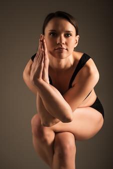 Любитель йоги делает garudasana на темном фоне