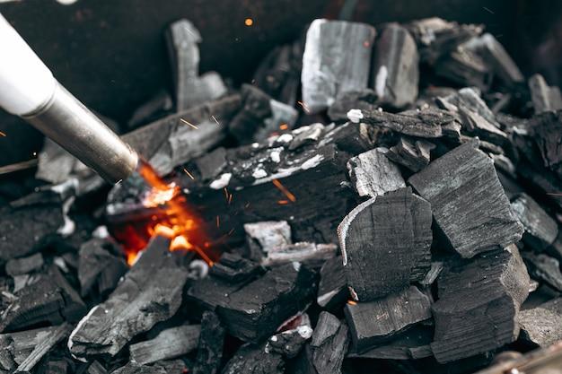 ガスバーナーはグリルで石炭を点火しています