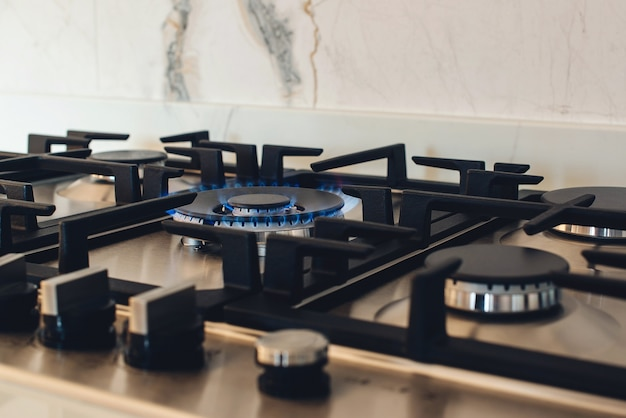 プロパンガスの炎を燃やすガス炊飯器。モダンなキッチンの新しいガスストーブ器具とカウンタートップの表面。