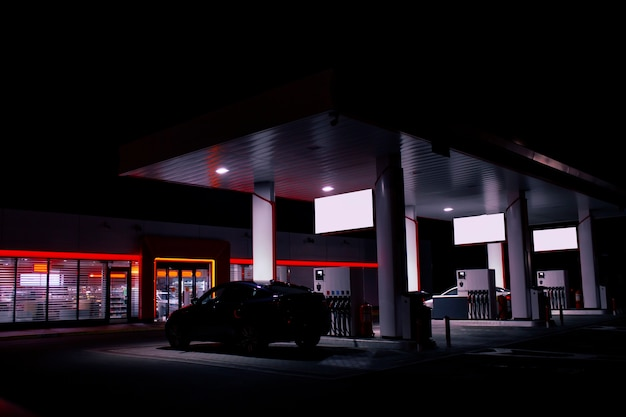 A gas hose is installed in a car at a night gas station with a store bright lights.