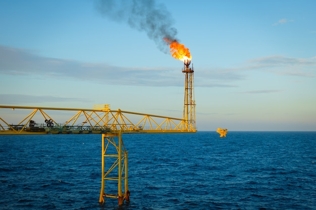 Gas is releasing and burning to the atmosphere from flare bridge of offshore gas platform