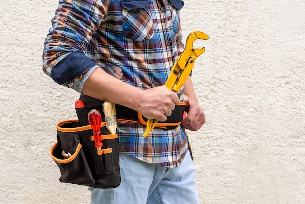 Газовый ключ в руках рабочего с инструментами. гаечный ключ в руках строителя в клетчатой синей рубашке.