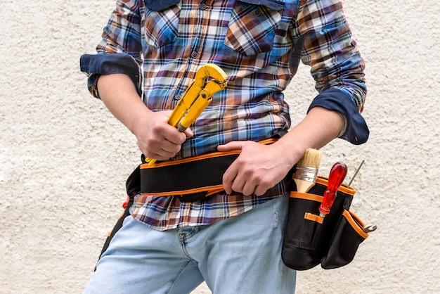Газовый ключ в руках рабочего с инструментами.
