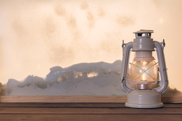 Gas lantern on wooden board near heap of snow through window
