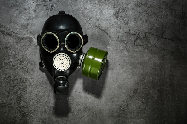 Gas mask on a black stone background with a green filter cartridge. post-apocalyptic concept.