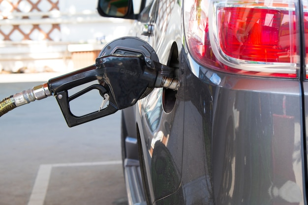 Gas nozzle pumping gas into a  car