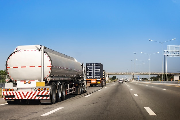 Gas or oil truck on highway road with container.