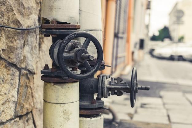 거리에 검은색 밸브가 있는 가스 파이프