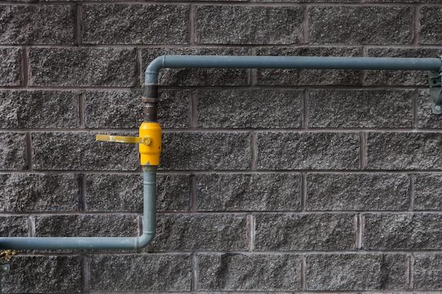 建物の壁にガス管。住宅の壁に黄色のガスパイプラインバルブ。