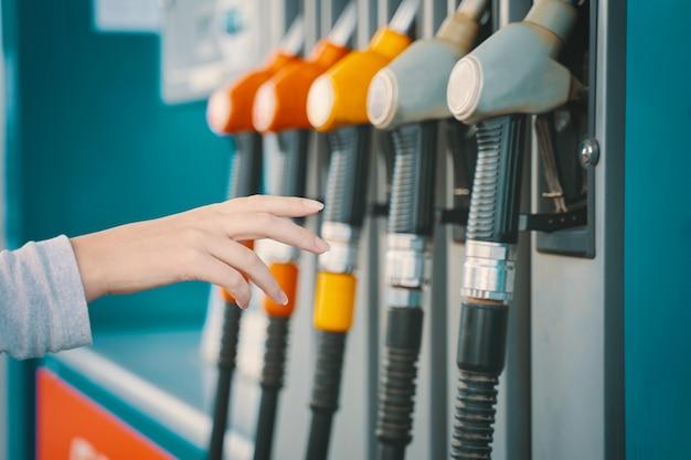 ガソリンスタンド。人間の手がガスポンプの充填ノズルに手を伸ばします。車に燃料を補給する女性。