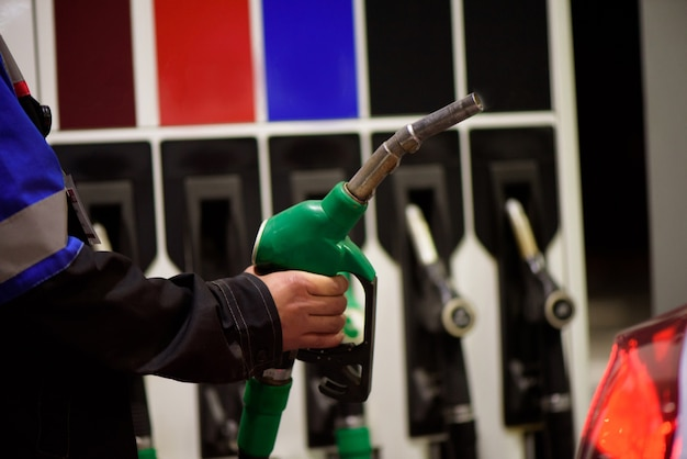 仕事中のガソリンスタンドの係員。ガソリンスタンドでの車の給油。