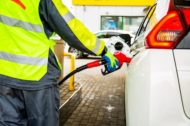 가솔린으로 차에 연료를 공급하는 작업복을 입은 주유소 직원이 얼굴을 닫습니다.