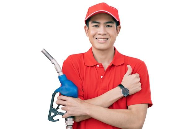 ガソリンスタンドの男性男性幸せな労働者のスタッフは、燃料ノズルを処理し、クリッピングパスで白い背景に分離された親指を立てる
