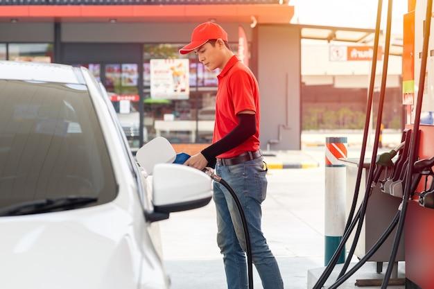 ガソリンスタンド男性男性労働者スタッフ幸せなサービス作業車ガソリン燃料を旅行者の車に補充