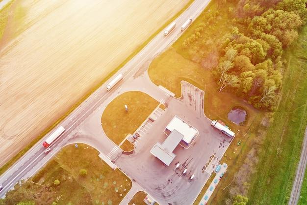 Автозаправочная станция возле шоссе с движущимися автомобилями с высоты птичьего полета