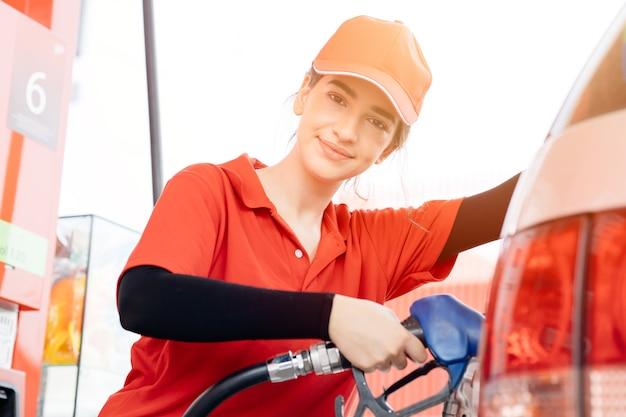 ガソリンスタンドの女性労働者スタッフ幸せなサービス作業は旅行者に車のガソリン燃料を補充します