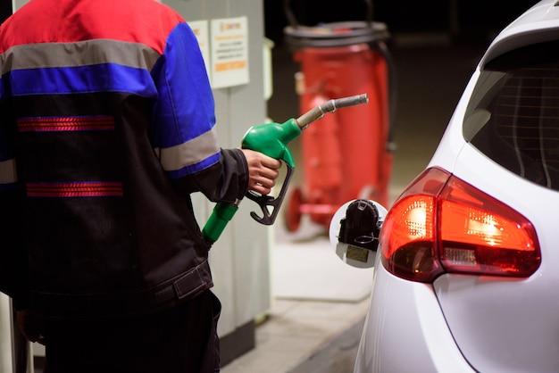 Работник азс в спецодежде заправляет роскошный автомобиль бензином, держащим заправочный пистолет на станции.