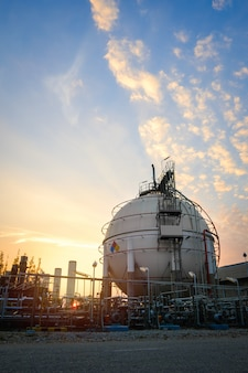 Gas storage sphere tanks in oil and gas refinery industrial plant with sunset sky