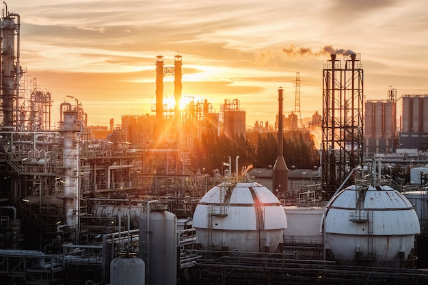 Gas storage sphere tanks in petrochemical industry or oil and gas refinery plant at evening, manufacturing of petroleum industrial plant with gas column and smoke stacks on sunset sky
