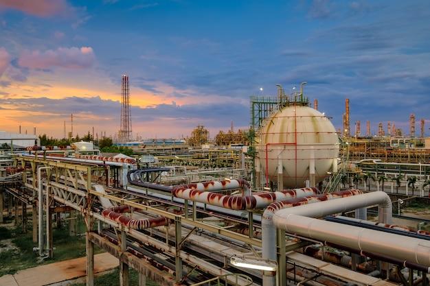 Резервуар для хранения газа и трубопровод на нефтеперерабатывающем заводе на закате