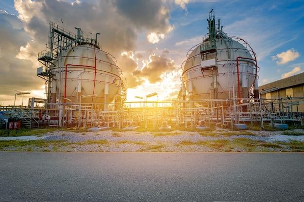 일몰 시 정유 산업 공장의 가스 저장 탱크 및 파이프라인