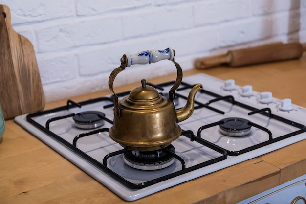 On the gas stove is a copper kettle with a beautiful handle.