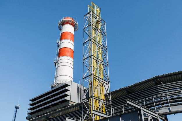 Gas turbine power plant on natural gas with chimneys of red white color against a blue sky on a sunny day