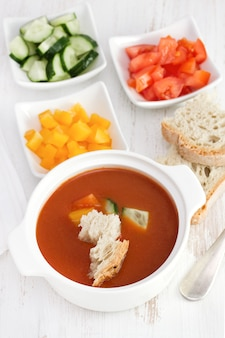 Gaspacho with bread and vegetables in white bowl
