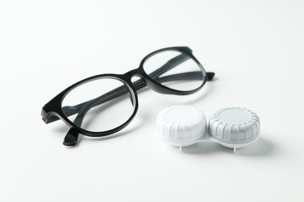 Gasses and contct lenses on white surface, close up