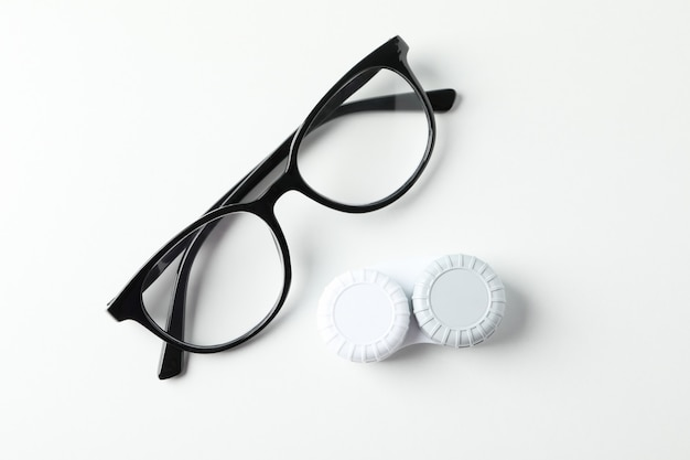 Gasses and contct lenses on white surface, top view