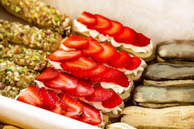 달콤한 에끌레어가 포함된 미식 상자: 치즈 무스, 신선한 딸기, 초콜릿 코팅 크림, 피스타치오 부스러기
