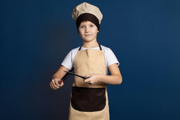 Концепция гастрономии, кулинарии, общественного питания и пищевой промышленности. студийный снимок красивого симпатичного 10-летнего мальчика, одетого в униформу шеф-повара, точит нож с другим. дети мужского пола, оттачивающие кухонные ножи