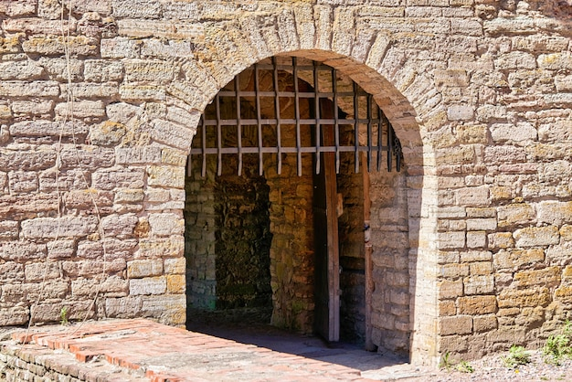 A gate with a thick metal lattice covering the entrance to the fortress. red brick fortress wall with gates