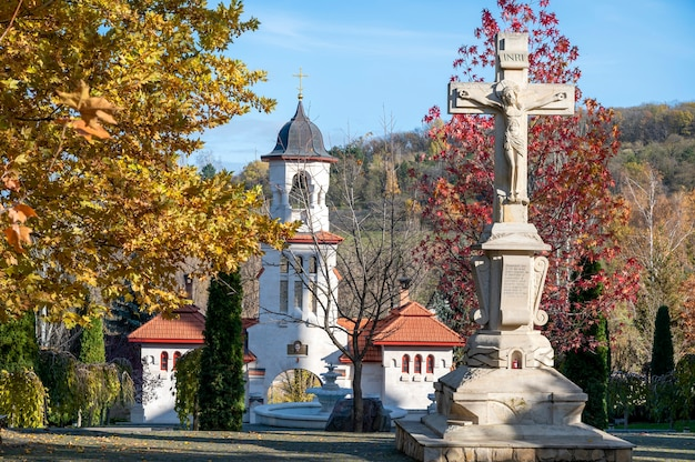 Gates of the churchi monastery. a lot of green buches and colored trees, stone cross in the center. good weather in moldova