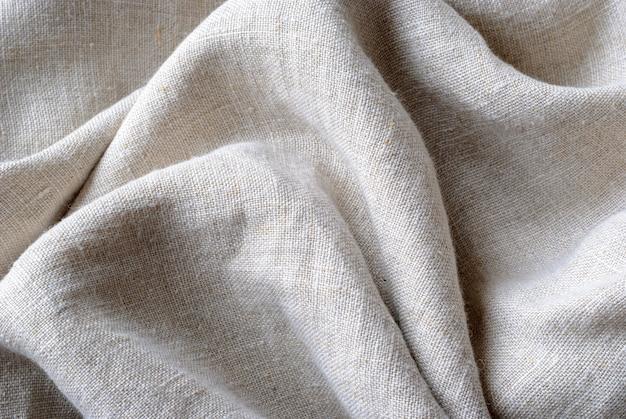 Собранная и сложенная текстура тканого льняного полотна