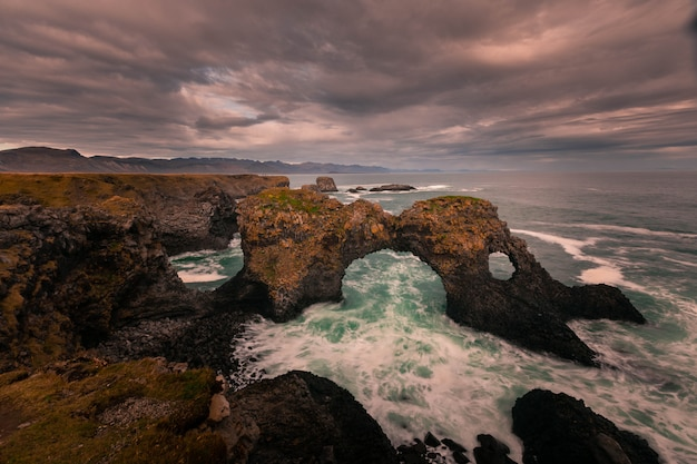 Арка gatklettur в городе арнарстапи на полуострове снафеллснес, западная исландия.