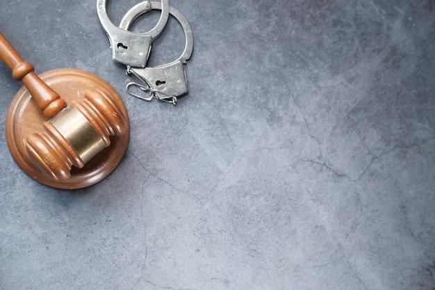 Молоток и наручники на столе с копией пространства