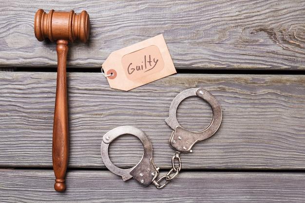 木製の背景にガベルと手錠。上面図フラットレイ。有罪の概念。