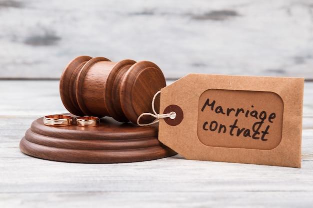 Молоток и брачный контракт остроумие кольца. фон белый деревянный стол.