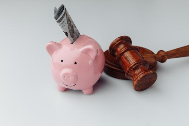 Молоток и розовая копилка с долларовой купюрой