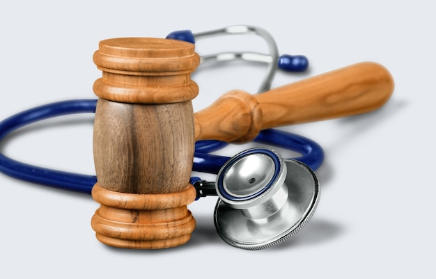 背景にガベルと聴診器、バングルと医療過誤のシンボル写真