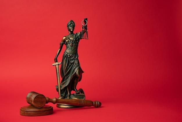 Молоток и статуя правосудия на красном фоне