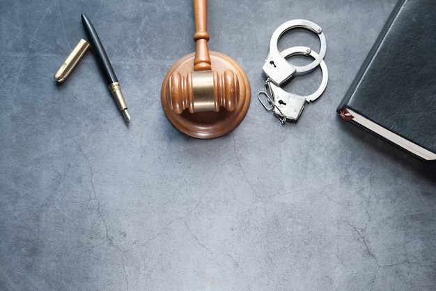 Молоток, книга и наручники на черном фоне сверху вниз