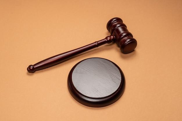 茶色の背景のスタンドにガベルダウン。法制度の正義の概念。スペースをコピーします。