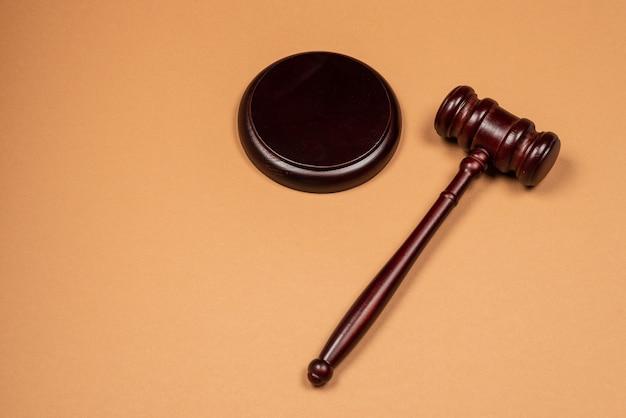 Молоток на подставку на коричневом фоне. концептуальная система правосудия. скопируйте пространство.