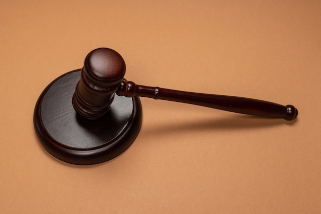 Gavel down on stand on brown background. justice of law system conceptual. copy space.
